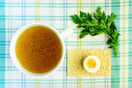 bouillon: Bouillon, broth, clear soup in a white cup with a loaf, parsley, boiled egg on the tablecloth. Close-up. Stock Photo