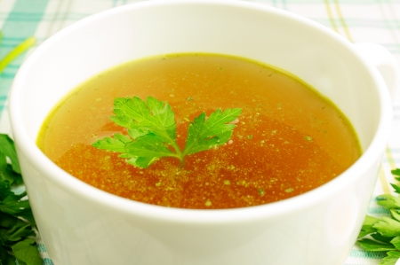 chicken's: Bouillon, broth, clear soup in a white cup with a loaf, parsley, boiled egg on the tablecloth. Close-up. Stock Photo