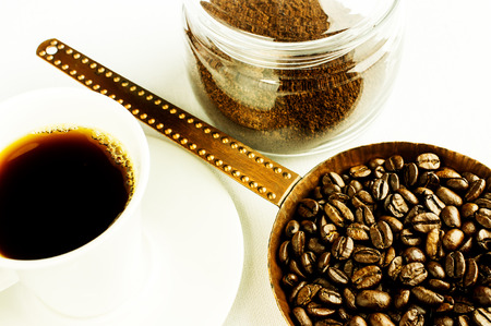 Coffee beans in an old copper pan. Ground coffee in a glass jar. Soluble coffee cup. photo