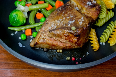 Beef fried with vegetables in a pan close-up with selective focus photo