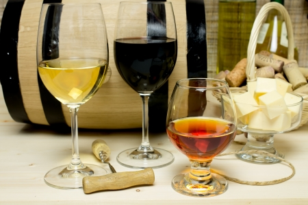 Red and white wine in glasses, brandy with a barrel and wine corks basket, bowl with cheese and a bottle of wine, a corkscrew. photo
