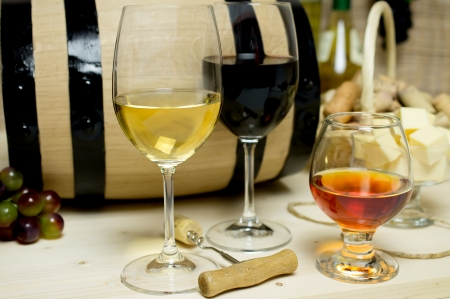 Red and white wine in glasses, brandy. On the background of a barrel and wine corks basket, bowl with cheese and a bottle of wine, a corkscrew. photo