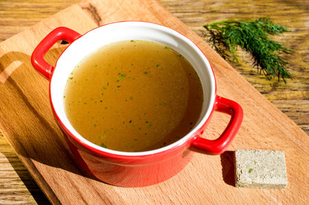 bouillon: Concentrated broth, bouillon, clear soup in a cup and a bouillon cube Stock Photo