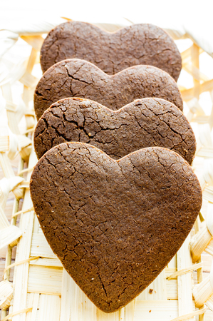 Chocolate chip cookies in the form of heart  in a basket. Several pieces close up. photo