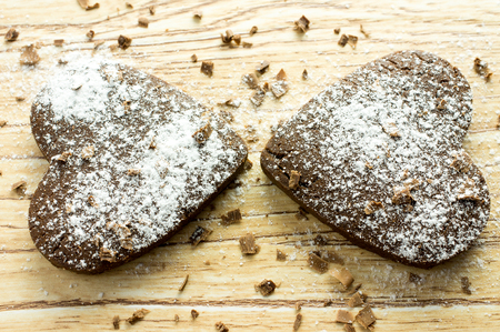 Two chocolate heart cookies in powdered sugar and chocolate crumbs. photo