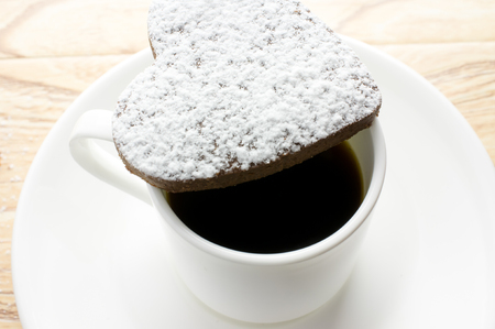 Chocolate heart cookies in powdered sugar in a coffee cup photo