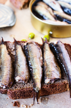 sprats: Sandwich with sprats on a table with a can of sprats