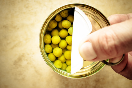 canned peas: Man opens canned peas hand