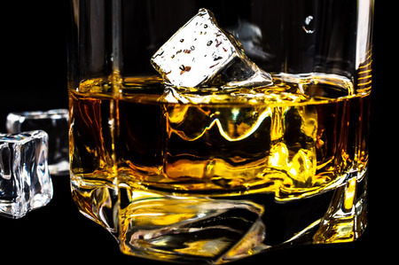 bourbon: Bourbon whiskey with ice on a black background
