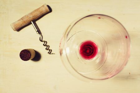 residue: Unfinished red wine in the glass on the table with a corkscrew and cork