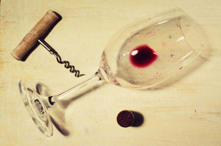 emptied: Unfinished red wine in the glass on the table with a corkscrew and cork
