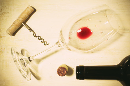 the residue: Unfinished red wine in the glass on the table with a corkscrew and cork