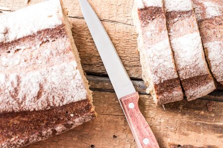Cutting of rye bread with a knife on a wooden board photo