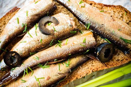 sardinas: Sandwich, tapas con sardinas, espadines con aceitunas y hierbas Foto de archivo