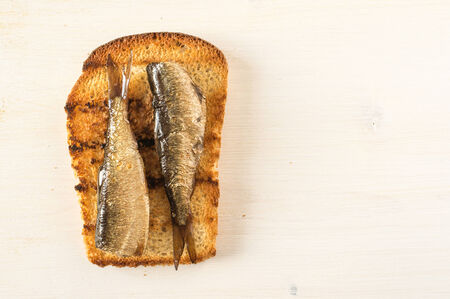 sprats: Sandwich with sardines on white wooden table and space for text