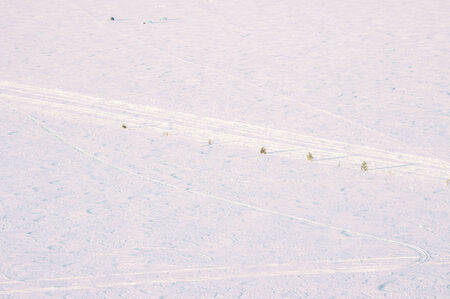 ski traces: Snow cover with traces of snowmobile and ski equipment. Ice crossing over the river