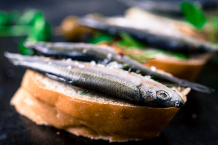 sprats: Tapas snack with fish sprats, parsley, dill and olives Stock Photo