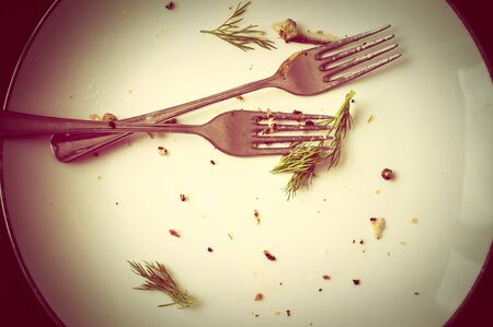 leftovers: Leftovers into an empty plate and two forks