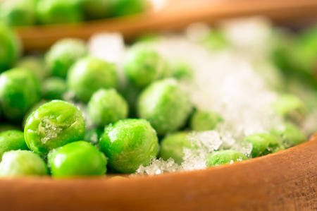 heap of snow: Frozen green peas with pieces of pods covered with frost