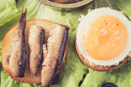 sardinas: Tapas, aperitivo pan de hamburguesa con huevo frito, sardinas o espadines Foto de archivo
