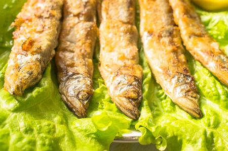 sardinas: Sardinas a la plancha sobre la lechuga y limón Foto de archivo