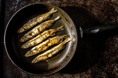 sardinas: Sardinas a la brasa en una sart�n en un plato negro. Vista superior