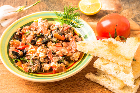 hot peppers: Tapas, Spanish appetizer of fish and vegetables in a bowl on a table with tomatoes and hot peppers. Stock Photo