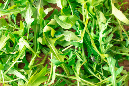 roquette: Arugula salad fresh on a wooden table top view Stock Photo