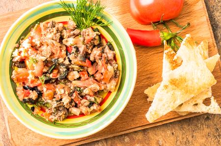 chiles picantes: Tapas, aperitivo español de pescado y verduras en un recipiente sobre una mesa con tomates y chiles.