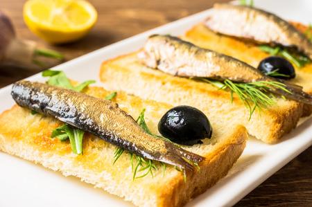 sardinas: Sardinas ahumadas en tostadas frito con aceitunas, r�cula y eneldo Foto de archivo