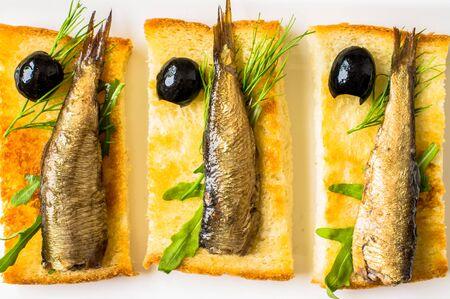 sardinas: Sardinas ahumadas en tostadas frito con aceitunas, rúcula y eneldo Foto de archivo