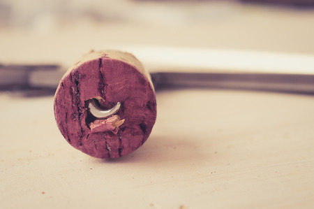 sommeliers: Cork from red wine with a protruding tip of the steel corkscrew. Pastel colors filter