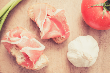 spanish onion: Spanish jamon snacks on a wooden table with tomato, green onion and garlic. Top view. Filter pastel