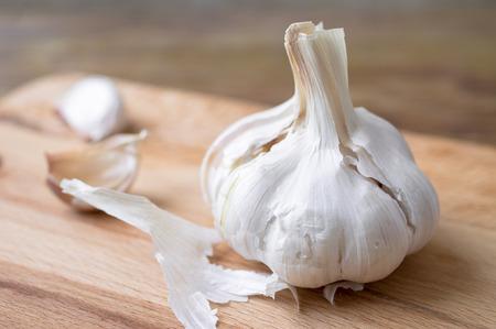ajos: Diente de ajo y los dientes de ajo y la c�scara en una tabla de madera