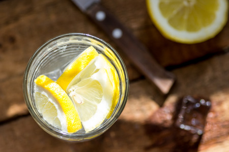 fruit in water: Water with lemon slices and ice view from above. Rustic Style