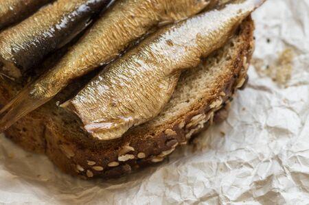 sardinas: Sardinas en un pedazo de pan en primer plano en papel