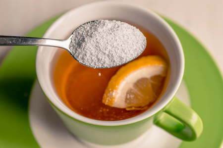 dissolve: Sweetener is poured from a spoon in a cup of tea Stock Photo