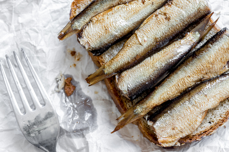 sprats: Sandwich with sprats and fork top view close-up Stock Photo