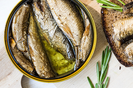 gold cans: Can with smoked sardines and sandwich with a sprig of rosemary top view Stock Photo
