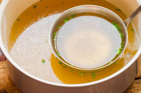 huesos: Cacerola con el caldo con una cuchara en la tabla