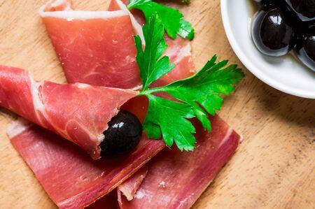 serrano: Jamon Serrano with herbs and olives for tapas closeup Stock Photo
