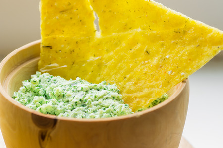 corn chips: Corn chips in a bowl with green sauce closeup Stock Photo