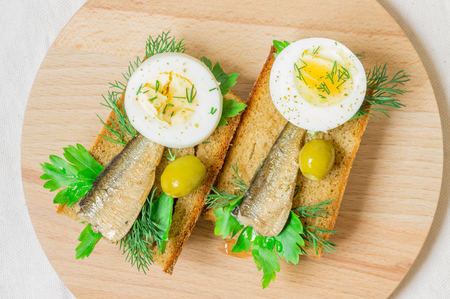 sardines: Tapas with sardines on toast with green olives and egg Stock Photo