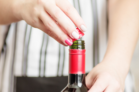 Female hand unscrews the screw cap red wine bottle