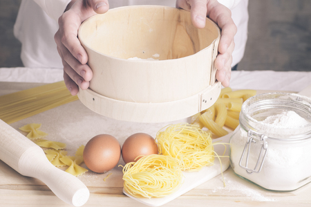 sift: Hands chef cooking pasta dough sift flour Stock Photo