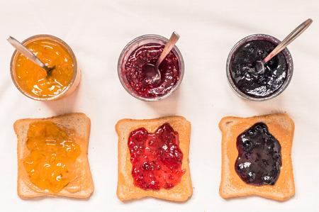 mermelada: S�ndwiches de pan tostado con mantequilla de man� y mermelada de frambuesa, ar�ndanos, vista desde arriba de naranja Foto de archivo