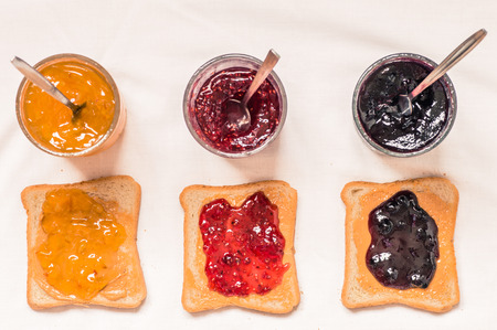jam: Toast sandwiches with peanut butter and jam raspberry, blueberries, orange top view