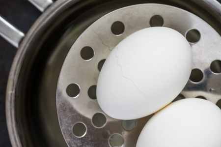 get out: Two eggs get out of the steel pan top view