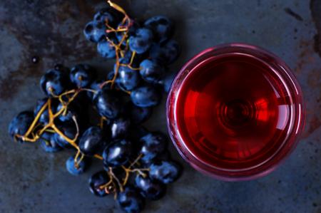 Glas van jonge rode wijn met druiven op de top Stockfoto