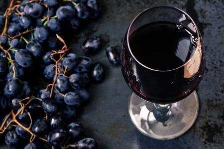 copa de vino: Copa de vino tinto con uvas en el fondo negro Foto de archivo